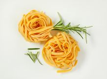 Dried ribbon pasta. Bundles of dried ribbon pasta on white background royalty free stock image