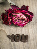Dried rose and chocolate word YOU Stock Photography