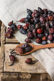 Dried rose hips scattered on wood background over linen cloth, spoon with fruits Stock Photos