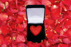Dried rose petal background with glitter heart in box Stock Images