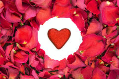 Dried rose petals in a circle with glitter heart in the centre. stock photo