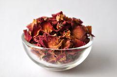 Dried rose petals in a clear glass bowl Stock Image