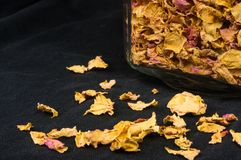 Dried rose petals in a glass jar with lid. On a black background stock photos