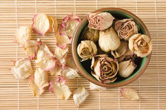 Dried rosebuds in teacup and petals top view Royalty Free Stock Image
