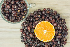 Dried rosehips and sliced orange arranged in the two bowls, heal Stock Photography