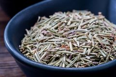 Dried Rosemary herb in black bowl close up Stock Image