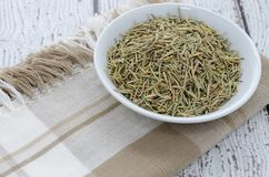 Dried Rosemary Herb. Dried rosemary spice herb in a white bowl on napkin. Wooden background and copy space Stock Photography
