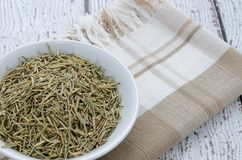 Dried Rosemary Spice. Herb in a white bowl on napkin.  Copy space Stock Photo