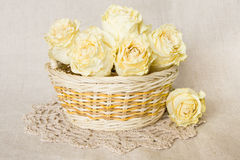 Dried roses in basket with doily Stock Photo