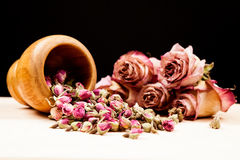 Dried roses and buds with wooden objects Stock Images