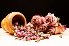 Dried roses and buds with wooden objects Royalty Free Stock Photos
