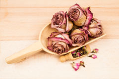 Dried roses and buds with wooden objects Stock Photos
