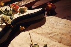 Dried roses on electric guitar and vintage sheet music closeup