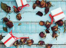 Dried roses with gift boxes on blue wooden parquet planks Royalty Free Stock Image