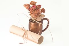 Dried roses in metal cup and scroll. Lying on white background Royalty Free Stock Photos