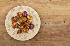 Dried roses on plate, wood Stock Image