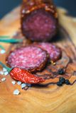 Dried salami crusted in ground red pepper. On dark background royalty free stock photo
