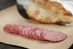 Dried salami sausage on paper ready for sandwich Royalty Free Stock Photos