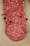Dried salami sausage on paper ready for sandwich. Rustic style royalty free stock photo