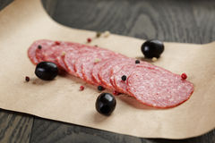 Dried salami sausage on paper ready for sandwich. Rustic style royalty free stock photography