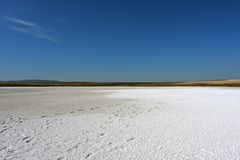 Dried salt lake under a bright blue sky. stock photos