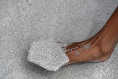 Dried sand balanced on a foot at the beach stock images