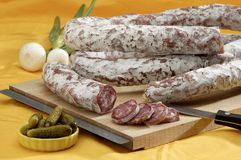 Dried Sausage. Lengths of dried sausage arranged on wooden cutting board with knife, onions and pickles visible Stock Photo