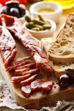 Dried sausage and country bread on wooden board Stock Photo