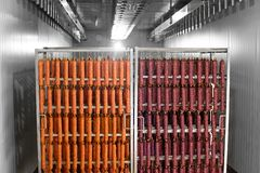Dried sausage hanging on a rope on a metal frame in the smoke house. stock image