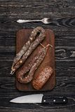 Dried sausage, knife and fork Royalty Free Stock Image