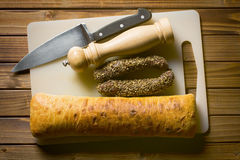 Dried sausages with ciabatta on cutting board Royalty Free Stock Images