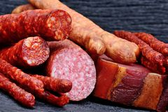 Dried sausages with salami and prosciutto on table. Dried sausages with salami and prosciutto on a wood table Stock Photography