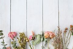 Dried shabby chic flowers white wooden background Stock Photo
