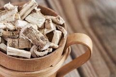 Dried and sliced marshmallow root. Close-up of marshmallow root Althaea officinalis in wooden cup. Copy space Stock Photos