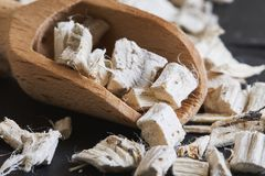Dried and sliced marshmallow root. Althaea officinalis in wooden scoop Stock Photos