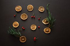 Dried slices of oranges on dark brown black background with red stock photo