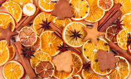 Dried slices of oranges, lemons, star anise, cinnamon sticks and gingerbreads on beige background Stock Image