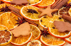 Dried slices of oranges, star anise, cinnamon sticks and gingerbreads on beige background, Christmas background Stock Image
