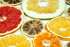 Dried slices of various citrus fruits on white backgroun. The Dried slices of various citrus fruits on white backgroun royalty free stock photography
