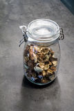 Dried spice and plant material in glass jar with closed lid for royalty free stock images