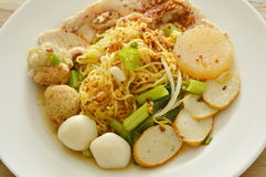 Dried spicy Chinese egg noodles topping fish and shrimp ball with slice boiled pork on plate. Dried spicy Chinese egg noodles topping fish and shrimp ball with Royalty Free Stock Photo
