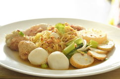 Dried spicy Chinese egg noodles topping fish and shrimp ball with slice boiled pork on plate. Dried spicy Chinese egg noodles topping fish and shrimp ball with Stock Image