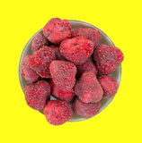 Dried strawberries in bowl on yellow Stock Photo