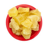 Dried Sugared Pineapple Chunks. A top view of a red bowl filled with pineapple chunks on a cutting board royalty free stock photography
