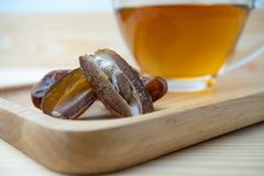 Dried of sweet dates palm fruits and tea cup on wooden plate. Dates is a dried fruit that provides high energy.  royalty free stock images