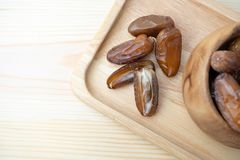 Dried of sweet dates palm fruits on wooden plate. Dates is a dried fruit that provides high energy.  stock photography