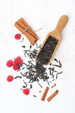 Dried tea leaves, cinnamon and raspberries on a white wooden bac. Kground, top view, vertical Stock Image