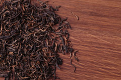 Dried tea leaves on wooden background Royalty Free Stock Photo