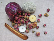 Dried  tearoses flowers scattered on linen. Dry roses flowers scattered on linen with candles stone and piece of  bark Stock Images