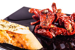 Dried Tomatoes on a black plate with bread Stock Photo